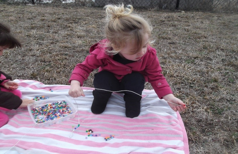 using a stick for stringing beads journeyintoearlychildhood.com